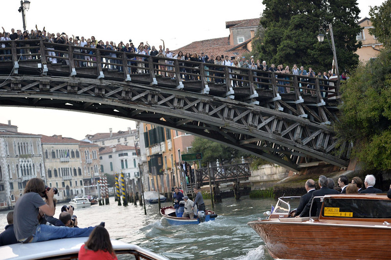 """. People wave from a bridge to US actor George Clooney standing on a taxi boat on the Grand Canal on his way to the Aman hotel on September 27, 2014 in Venice where Clooney and British fiancee, Amal Alamuddin celebrate their wedding. George Clooney has said goodbye to bachelorhood in Venice with a stag party at his favorite restaurant with Hollywood chums, and was gearing up for a day of glamorous pre-wedding celebrations. The actor had swept into the floating city yesterday with his British fiancee Amal Alamuddin on a watertaxi dubbed \""""Amore\"""", zipping up the Grand Canal to cheers from fans at the start of nuptials set to draw out over the weekend.  ANDREAS SOLARO/AFP/Getty Images"""