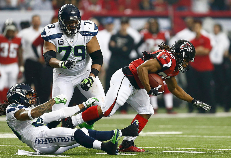 . Atlanta Falcons running back Jacquizz Rodgers (R) breaks free from Seattle Seahawks Earl Thomas (L) and Red Bryant (79) during the first quarter in their NFL NFC Divisional playoff football game in Atlanta, Georgia January 13, 2013. REUTERS/Chris Keane