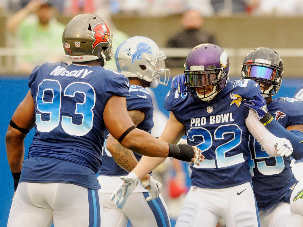 . NFC defensive tackle Gerald McCoy (93), of the Tampa Bay Buccaneers, congratulates safety Harrison Smith (22), of the Minnesota Vikings, after Smith scored a touchdown, during the first half of the NFL Pro Bowl football game against the AFC, Sunday, Jan. 28, 2018, in Orlando, Fla. (AP Photo/Steve Nesius)