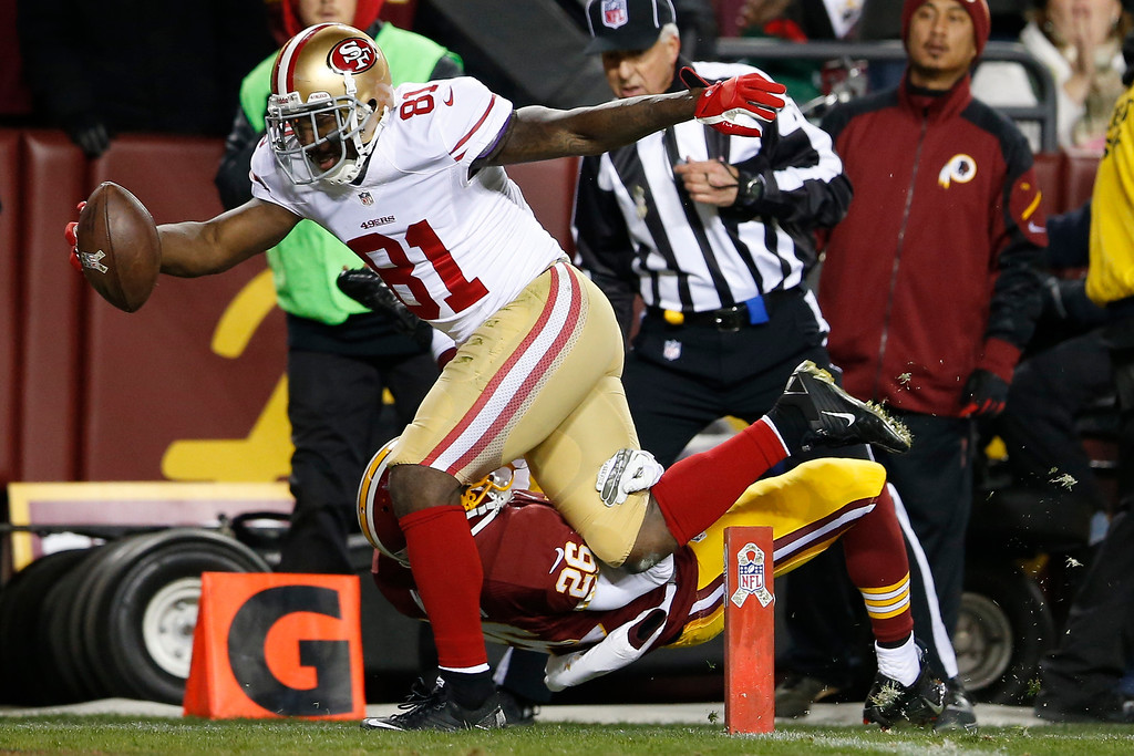 . San Francisco 49ers wide receiver Anquan Boldin lands in the end zone with a touchdown pass as Washington Redskins cornerback Josh Wilson hits the turf during the first half of an NFL football game in Landover, Md., Monday, Nov. 25, 2013. (AP Photo/Evan Vucci)