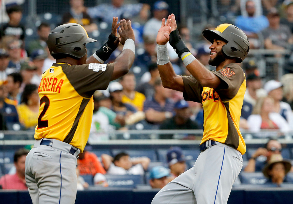 . World Team\'s Amed Rosario, of the New York Mets, right, high fives teammate Dilson Herrera, of the New York Mets, after scoring on an RBI base hit by Raimel Tapia during the ninth inning of the All-Star Futures baseball game, Sunday, July 10, 2016, in San Diego. (AP Photo/Lenny Ignelzi)