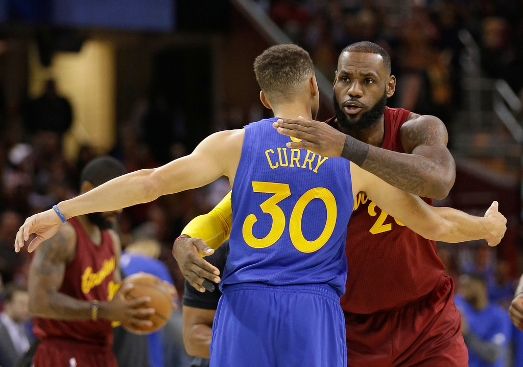 . Cleveland Cavaliers\' LeBron James, right, hugs Golden State Warriors\' Stephen Curry before an NBA basketball game, Sunday, Dec. 25, 2016, in Cleveland. (AP Photo/Tony Dejak)
