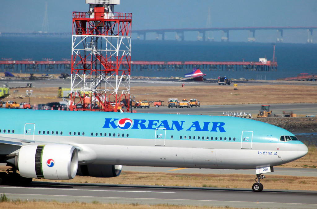 . A Korean Air jet lands on a runway across from the tail section of an Asiana Airlines jet that crashed earlier in the day at San Francisco International Airport Saturday afternoon, July 6, 2013.  (Karl Mondon/Bay Area News Group)