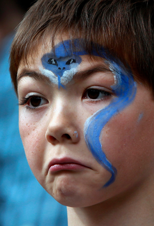 """. Aidan Land, 7, of San Carlos, wearing his Year of the Snake face paint, shows grudging admiration for the dragon dancers from the Asian Cultural Dance troupe performing at the Hakone Estate and Gardens a \""""Chinese Village Fair\"""" on Sunday afternoon, March 3, 2013 in Saratoga, Calif. (Karl Mondon/Staff)"""