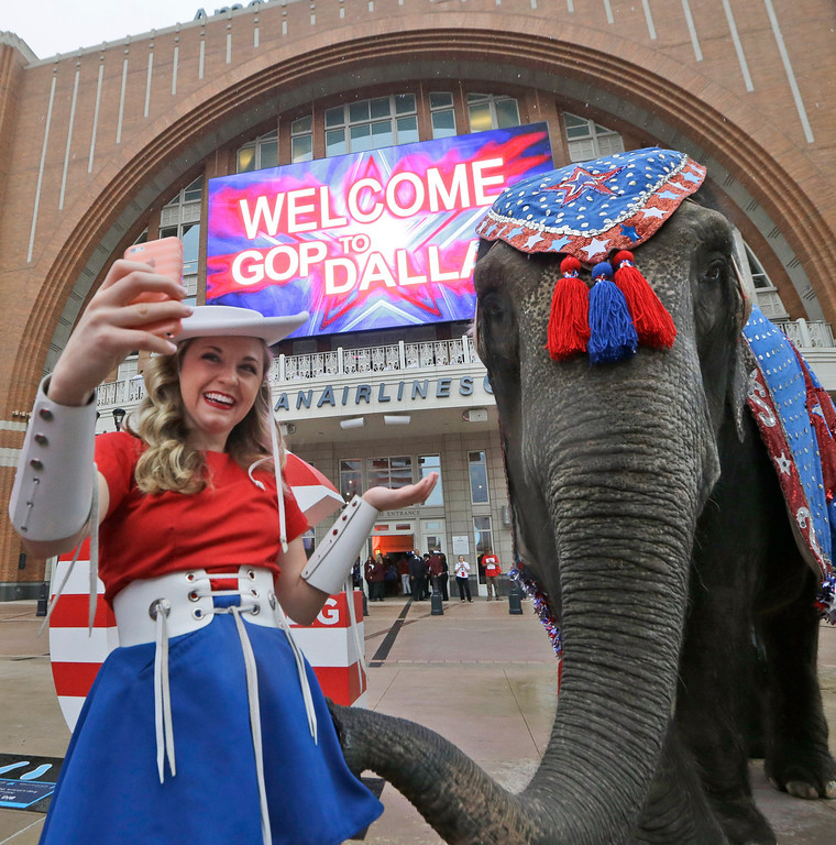 . Kilgore Rangerette Chelsea Crawford makes a selfie photo with an elephant in front of the American Airlines Center before a visit by members of the Republican National Committee scouting a 2016 Convention host site in Dallas, Thursday, June 12, 2014. American Airlines Center would serve as the convention site if Dallas\' bid is successful. Dallas is competing with Denver, Cleveland and Kansas City. (AP Photo/LM Otero)