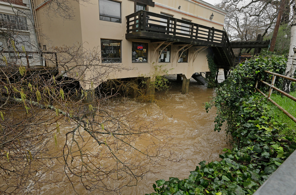 . Rising water in San Anselmo Creek flows beneath businesses built over it on Tuesday, Feb. 7, 2017, in San Anselmo, Calif. Flash flood watches are in place for parts of Northern California down through the Central Coast as heavy rains swamp roads and threaten to overtop rivers and creeks. The National Weather Service says more than an inch of rain could fall in the San Francisco Bay Area during a series of storms this week. (AP Photo/Ben Margot)