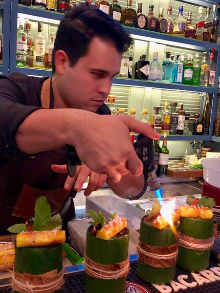Bartender mixes a tropical drink at a hotel bar in Panama.