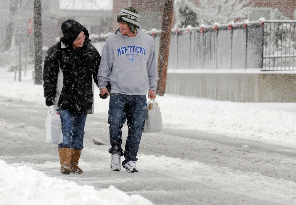 Description of . After a trip to the store, Brea Meadows, left, and Chris Terry enjoy a walk in the snow along 3rd Street in Henderson, Ky. Blizzard conditions moved through the Henderson area Wednesday, Dec. 26, 2012. (AP Photo/The Gleaner, Mike Lawrence)