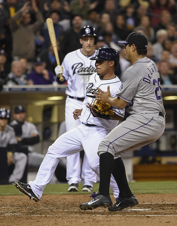 . SAN DIEGO, CA - APRIL 16:  Alexi Amarista #5 of the San Diego Padres scores past Jorge De La Rosa #29 of the Colorado Rockies on a wild pitch during the fifth inning of a  baseball game at Petco Park April 16, 2014 in San Diego, California.  (Photo by Denis Poroy/Getty Images)