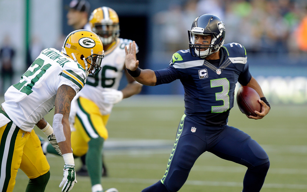 . Seattle Seahawks quarterback Russell Wilson (3) avoids Green Bay Packers\' Ha Ha Clinton-Dix (21) during the first half of an NFL football game, Thursday, Sept. 4, 2014, in Seattle. (AP Photo/Stephen Brashear)