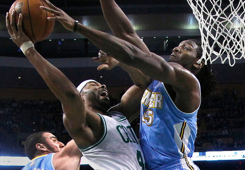 . Boston Celtics power forward Chris Wilcox, center, goes to the hoop against Denver Nuggets small forward Kenneth Faried, right, during the first half of an NBA basketball game in Boston, Sunday, Feb. 10, 2013. (AP Photo/Elise Amendola)