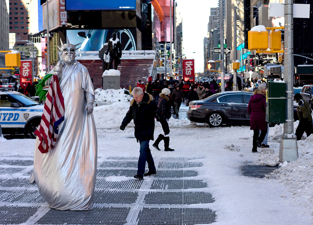 . A costumed character, along with pedestrians, navigate sometimes slippery conditions in New York\'s Times Square Sunday, Jan. 24, 2016, in the wake of a storm that dumped heavy snow along the East Coast. (AP Photo/Craig Ruttle)