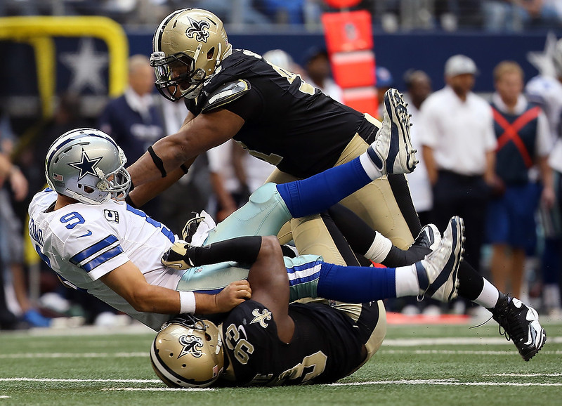 . Quarterback Tony Romo #9 of the Dallas Cowboys is sacked by defensive end Will Smith #91 of the New Orleans Saints and defensive tackle Junior Galette #93 of the New Orleans Saints at Cowboys Stadium on December 23, 2012 in Arlington, Texas. The New Orleans Saints beat the Dallas Cowboys 34-31 in overtime. (Photo by Tom Pennington/Getty Images)