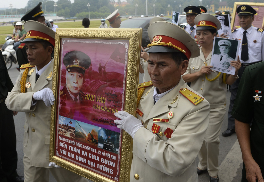 . Veterans hold portraits of late General Vo Nguyen Giap as they line up along a street to pay their final respects in Hanoi on October 10, 2013. The death of Vietnam\'s last great independence leader has sparked a battle over his legacy, with the regime seeking a girm grip on his image as communist hero, and brushing aside his criticism of the party in later life. HOANG DINH NAM/AFP/Getty Images
