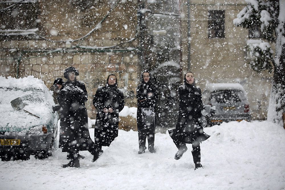 Description of . Ultra-orthodox Jews enjoy the snow in the Mea Shearim religious neighborhood of Jerusalem on January 10, 2013. Jerusalem was transformed into a winter wonderland after heavy overnight snowfall turned the Holy City and much of the region white, bringing hordes of excited children onto the streets. MENAHEM KAHANA/AFP/Getty Images