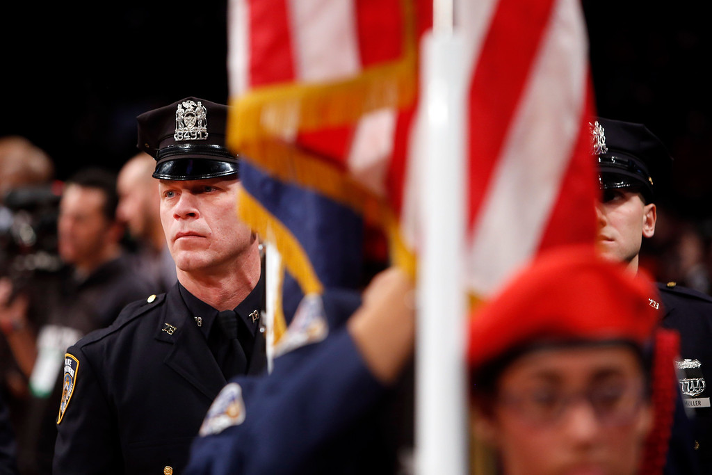 . New York Police Department officers Mark Cava, left, and Jason Muller wait on the sideline before participating in a moment of silence for two slain NYPD officers before an NBA basketball game between the Brooklyn Nets and the Detroit Pistons Sunday, Dec. 21, 2014, in New York.  A gunman ambushed NYPD officers Rafael Ramos and Wenjian Liu in Brooklyn Saturday, fatally shooting them as they sat in their patrol car before running into a nearby subway station and killing himself. (AP Photo/Jason DeCrow)
