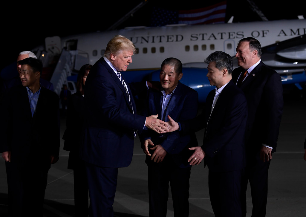 . President Donald Trump, center left, shakes hands with Kim Hak Song with Tony Kim, far left, and Kim Dong Chul, center, three Americans detained in North Korea for over a year, as they arrive at Andrews Air Force Base in Md., Thursday, May 10, 2018. Vice President Mike Pence, behind Tony Kim, and his wife Karen Pence, behind Trump, and Secretary of State Mike Pompeo, far right, were also at the air force base to greet them. (AP Photo/Susan Walsh)
