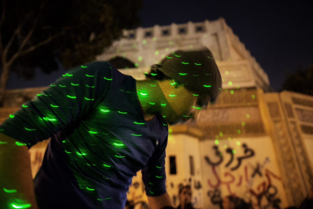 Description of . An Egyptian opposition supporter is pictured through green laser lights as he takes part in a demonstration on December 18, 2012 in front of the Cairo palace of Islamist President Mohamed Morsi in a last-ditch bid to scuttle the draft constitution being put to a referendum.  MARCO LONGARI/AFP/Getty Images