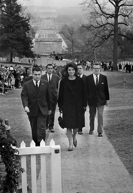 . Jacqueline Kennedy walks to the grave of her slain husband, President John F. Kennedy, in Arlington National Cemetery, Arlington, Va., Nov. 28, 1963. Others, from left, are: Pierre Salinger, White House press secretary; Secret Service agent Clinton J. Hill; and presidential aides Jack McNall and Lawrence O\'Brien. Ropes keep ordinary mourners at a distance on the hillside overlooking Memorial Bridge to Washington and the Lincoln Memorial in background.   (AP Photo/Bob Schutz)