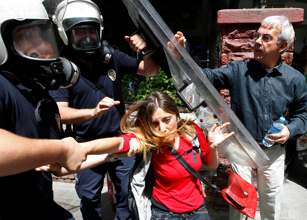 . Riot police detain a protester during a protest against Turkey\'s Prime Minister Tayyip Erdogan and his government\'s policy on Syria, in Ankara May 18, 2013. Erdogan said on Friday it would be up to the U.N. Security Council to decide whether to establish a no-fly zone inside Syria and said he backed the involvement of Russia and China in planned peace talks. The man on right is a passer-by, who did not take part in the protest, but stopped to ask the police to release the protester. REUTERS/Umit Bektas