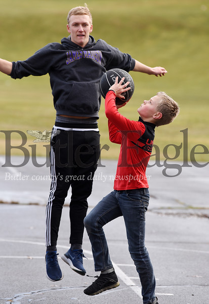 Harold Aughton/Butler Eagle: David Tomko, 10, of Butler attempts a shot against his cousin, Benjamin Overby, 19, a freshman at James Madison University during a friendly game of basketball at Father Marinaro Park, Monday, December 30, 2019.