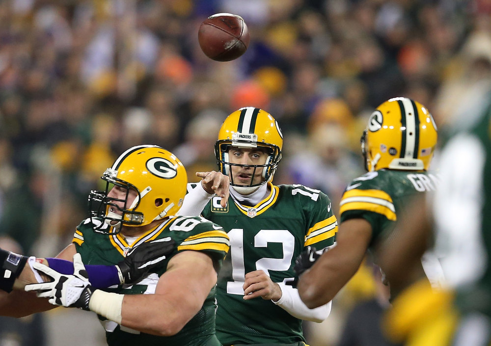 Description of . Quarterback Aaron Rodgers #12 of the Green Bay Packers throws the ball to running back Ryan Grant #25 in the first half against the Minnesota Vikings during the NFC Wild Card Playoff game at Lambeau Field on January 5, 2013 in Green Bay, Wisconsin.  (Photo by Andy Lyons/Getty Images)