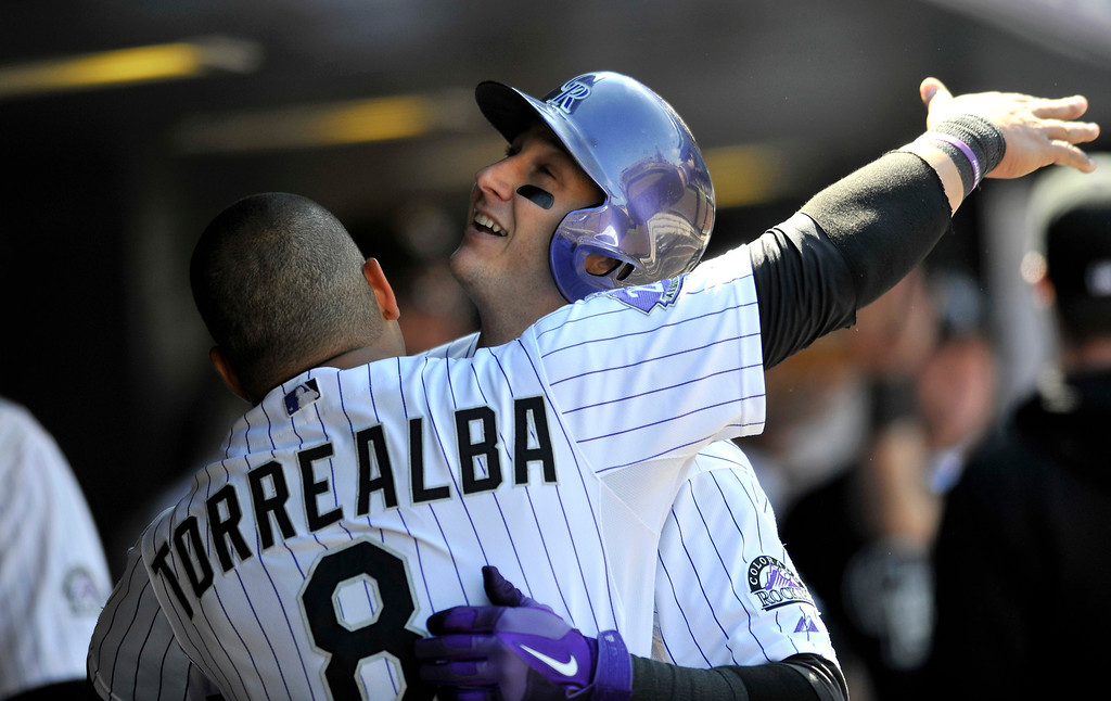 . Colorado Rockies\' Troy Tulowitzki (2) celebrates a two-run homer off St. Louis Cardinals starting pitcher Michael Wacha with teammate Yorvit Torrealba (8) during the third inning of a baseball game on Thursday, Sept. 19, 2013, in Denver. (AP Photo/Jack Dempsey)