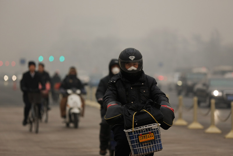 . Beijing residents wearing the masks rides a bicycle during severe pollution on February 25, 2014 in Beijing, China. The air pollution has caused an increase in the number of people seeking hospital treatment for respiratory problems and the public are asked to avoid outdoor activities.  (Photo by Lintao Zhang/Getty Images)