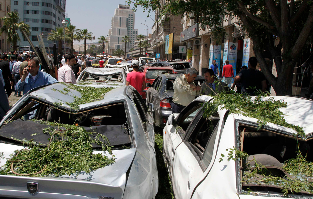 . People walk on a street lined with a damaged building and destroyed cars after a blast at Marjeh Square in Damascus April 30, 2013. The bomb in central Damascus killed 13 people on Tuesday, state television said, a day after Prime Minister Wael al-Halki survived an attack on his convoy in the heart of the Syrian capital. State television said 70 people were wounded, several critically. The British-based Syrian Observatory reported 9 dead civilians and 3 security men and said the death toll was likely to rise. REUTERS/Khaled al-Hariri