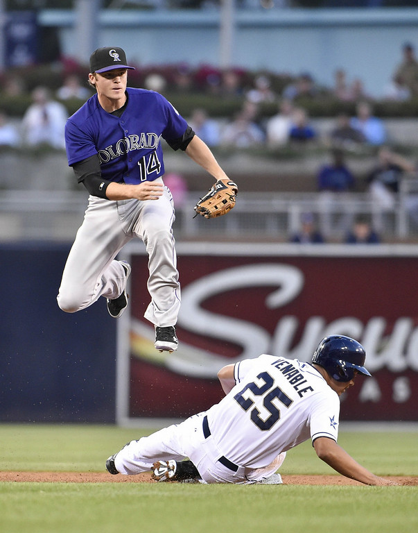 . Josh Rutledge #14 of the Colorado Rockies jumps over Will Venable #25 of the San Diego Padres as he turns a double play during the first inning of a baseball game at Petco Park August 11, 2014 in San Diego, California.  (Photo by Denis Poroy/Getty Images)