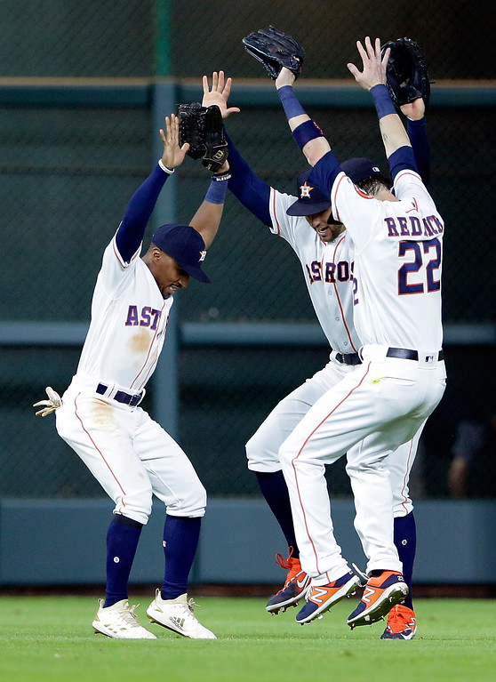 . Houston Astros outfielders Tony Kemp, left, George Springer and Josh Reddick, right, celebrate their 3-1 win against the Cleveland Indians after a baseball game, Sunday, May 20, 2018, in Houston. (AP Photo/Michael Wyke)
