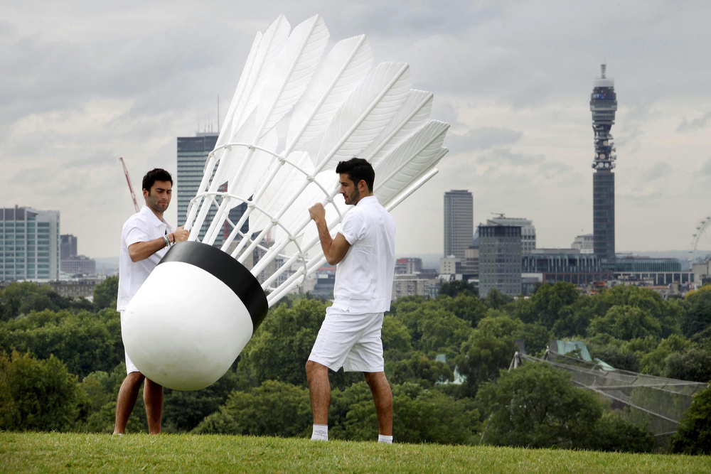 Description of . Jake Bernstone, left, and Adam Paris carry a giant shuttlecock - weighing over 30 kgs and measuring over 3 meters - on Primrose Hill, north London Wednesday July 13, 2011 to promote the World Badminton Championships, which will take place at London's Wembley Arena Aug. 8-14, 2011. The London Telecom tower is seen in the background.    (AP Photo/David Parry/PA Wire)
