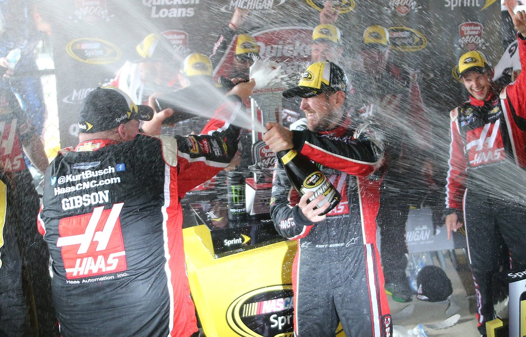 . Kurt Busch celebrates with teammates after winning the NASCAR Sprint Cup series auto race at Michigan International Speedway, Sunday, June 14, 2015, in Brooklyn, Mich. (AP Photo/Bob Brodbeck)