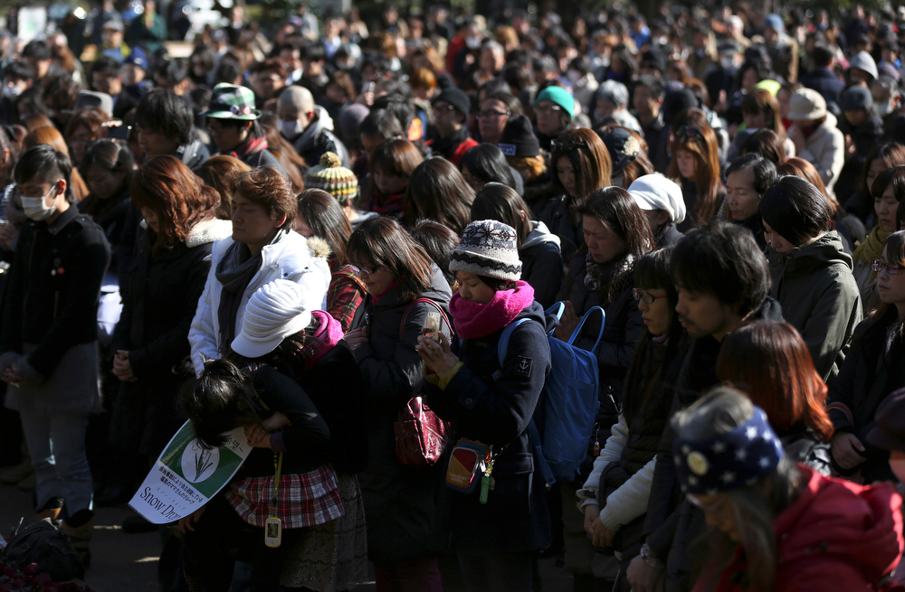 . People observe a moment of silence at 2:46 p.m. in Tokyo Tuesday, March 11, 2014, three years after a massive earthquake and tsunami struck northeastern Japan. Japan marked the third anniversary on Tuesday of a devastating disasters that left nearly 19,000 people dead or missing. (AP Photo/Eugene Hoshiko)