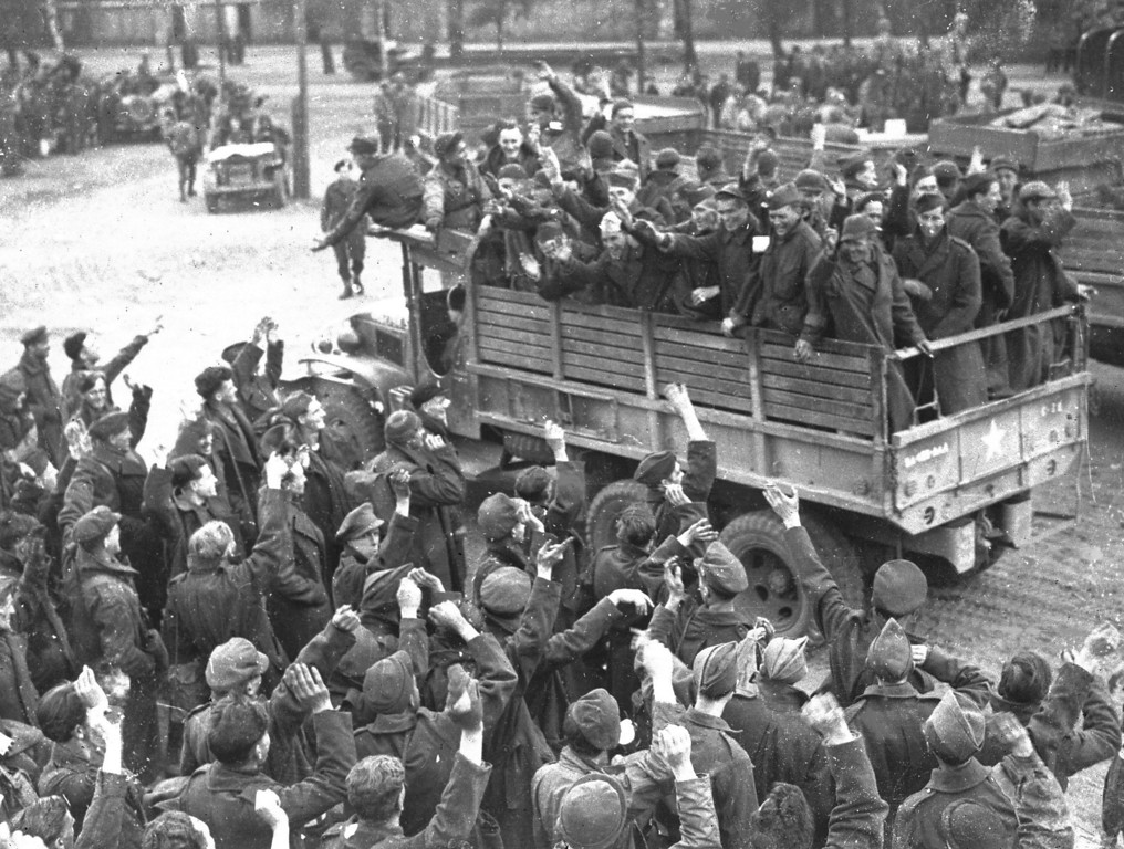 . British prisoners of war, foreground, bid farewell to fellow prisoners of war, a group of U.S. GIs, as the first U.S. truck leaves for Allied lines, at a camp at Altengrabow, Germany, May 7, 1945. About 19,000 Allied prisoners will be collected from the camp after consultations between U.S. and German officers revealed the captors could not sustain feeding the prisoners. (AP Photo/Henry L. Griffin)