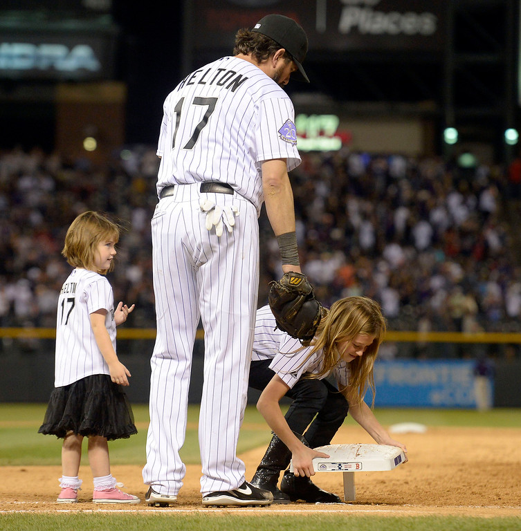 . Todd Helton (17) of the Colorado Rockies watches his daughter Tierney Faith pull up first base as Gentry Grace Helton (L) watches in the 9th inning of their game against the Boston Red Sox September 25, 2013 at Coors Field. The girls ran off the field with it as Helton watched. Helton will retire at the end of the season afer 17 years with the club. (Photo By John Leyba/The Denver Post)