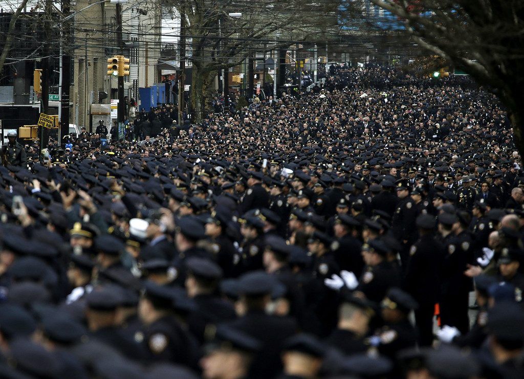 . Police officers line the streets near the funeral of Officer Wenjian Liu in the Brooklyn borough of New York, Sunday, Jan. 4, 2015. Liu and his partner, officer Rafael Ramos, were killed Dec. 20 as they sat in their patrol car on a Brooklyn street. The shooter, Ismaaiyl Brinsley, later killed himself.   (AP Photo/Seth Wenig)