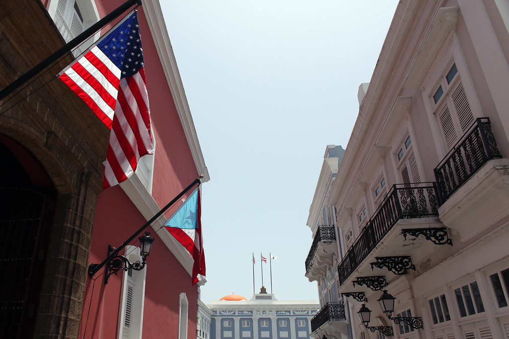 . The U.S. and Puerto Rico flags wave in front of the governor�s mansion in Old San Juan, Puerto Rico, Monday, June 29, 2015. International economists released a critical report on Puerto Rico\'s economy Monday on the heels of the governor\'s warning that the island can\'t pay its $72 billion public debt. (AP Photo/Ricardo Arduengo)