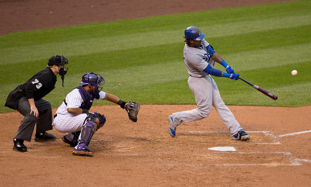 . Hanley Ramirez #13 of the Los Angeles Dodgers hits a solo home run as catcher Wilin Rosario #20 of the Colorado Rockies and home plate umpire Tripp Gibson look on during the sixth inning at Coors Field on June 8, 2014 in Denver, Colorado. (Photo by Justin Edmonds/Getty Images)