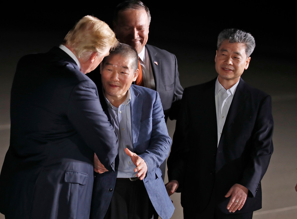 . President Donald Trump, accompanied by Secretary of State Mike Pompeo, back, shakes hands with former North Korean detainees Kim Dong Chul, with Kim Hak Song, upon their arrival, Thursday, May 10, 2018, at Andrews Air Force Base, Md. (AP Photo/Alex Brandon)