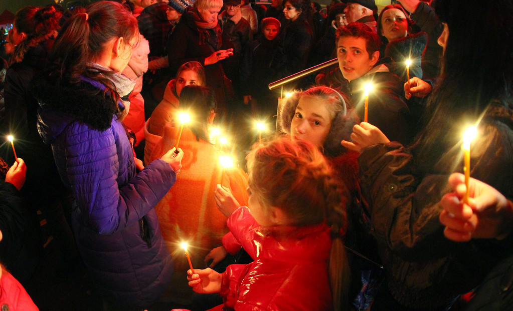 . People carry candles at the scene where the Maxima supermarket roof collapsed in Riga on November 22, 2013.  AFP PHOTO / PETRAS MALUKAS/AFP/Getty Images