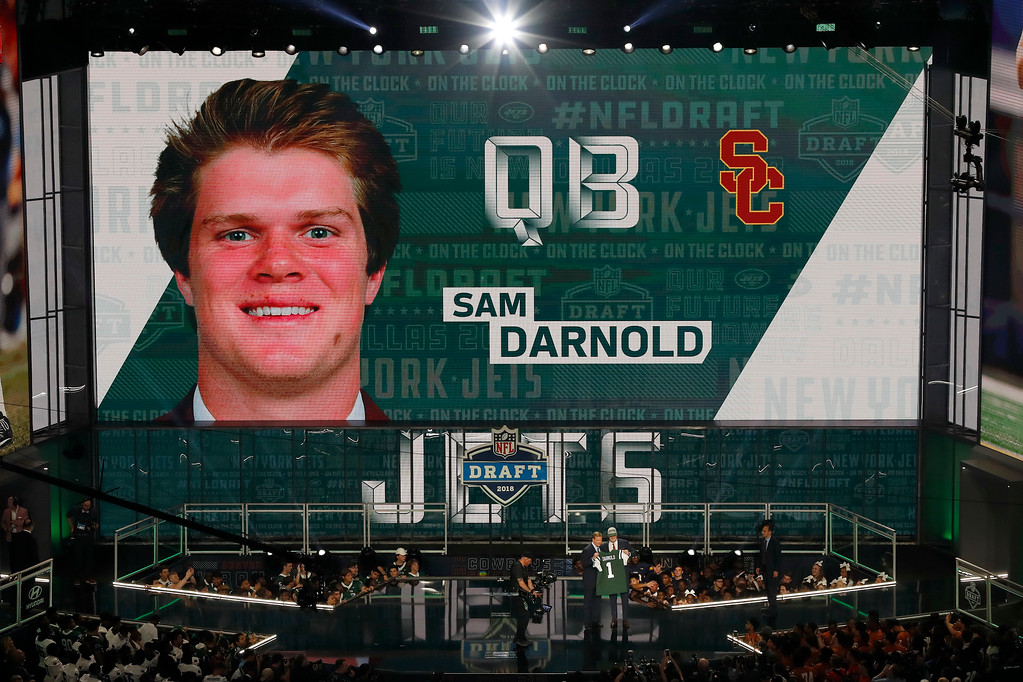 . USC\'s Sam Darnold is shown on the video screen as he is greeted on stage by Commissioner Roger Goodell after being picked by the New York Jets during the first round of the NFL football draft, Thursday, April 26, 2018, in Arlington, Texas. (AP Photo/David J. Phillip)