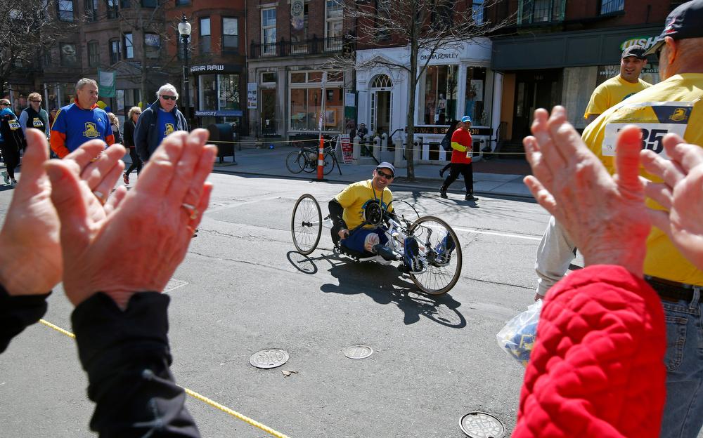 . Boston Marathon bombing survivor Marc Fucarile is applauded as he wheels himself during the Boston Marathon Tribute Run in Boston, Saturday, April 19, 2014. (AP Photo/Elise Amendola)