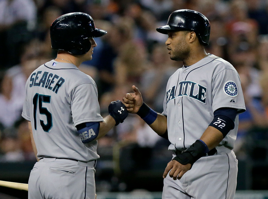 . Seattle Mariners\' Robinson Cano, right, is congratulated by Kyle Seager (15) after scoring against the Detroit Tigers during the ninth inning of a baseball game Saturday, Aug. 16, 2014, in Detroit. The Tigers defeated the Mariners 4-2. (AP Photo/Duane Burleson)
