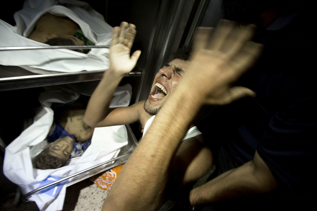 . A relatives of four Palestinian boys, all from the Bakr family, mourns over the body of one of the boys at the morgue of al-Shifa hospital in Gaza City, on July 16, 2014. Four children were killed and several injured at a beach in Gaza City medics said, in Israeli shelling witnessed by AFP journalists. The strikes appeared to be the result of shelling by the Israeli navy against an area with small shacks used by fishermen. The deaths raised the overall toll in nine days of violence in Gaza to 213. AFP PHOTO / MAHMUD HAMS/AFP/Getty Images