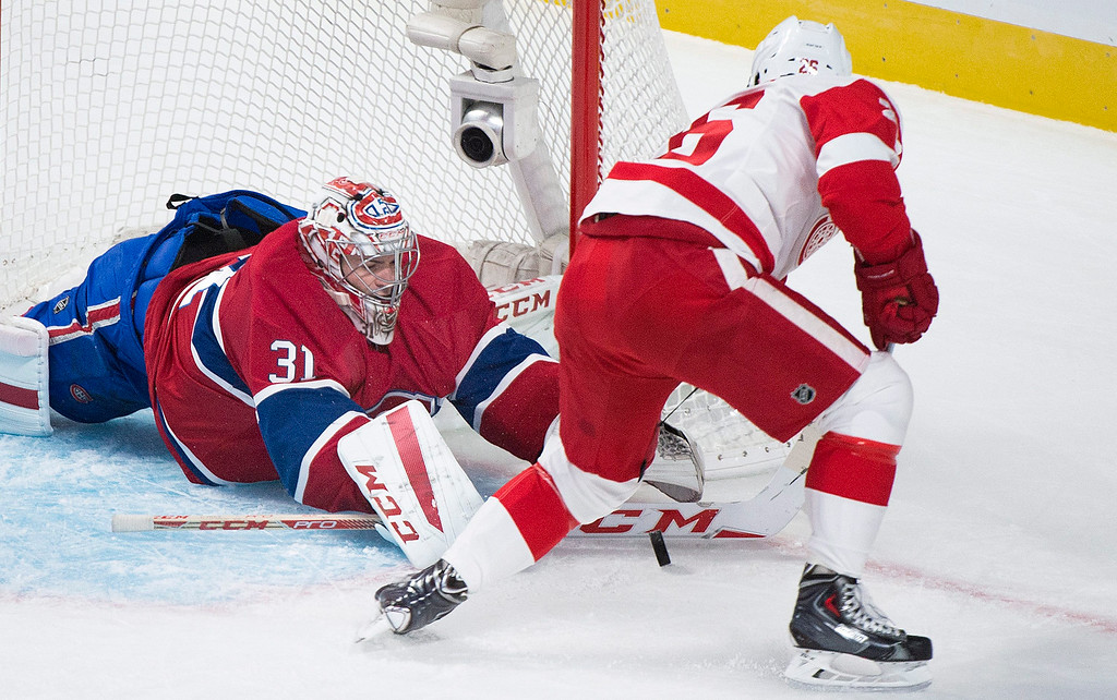 . Montreal Canadiens goalie Carey Price makes a save against Detroit Red Wings\' Tomas Jurco during first period NHL hockey action in Montreal, Tuesday, Oct. 21, 2104. (AP Photo/The Canadian Press, Graham Hughes)