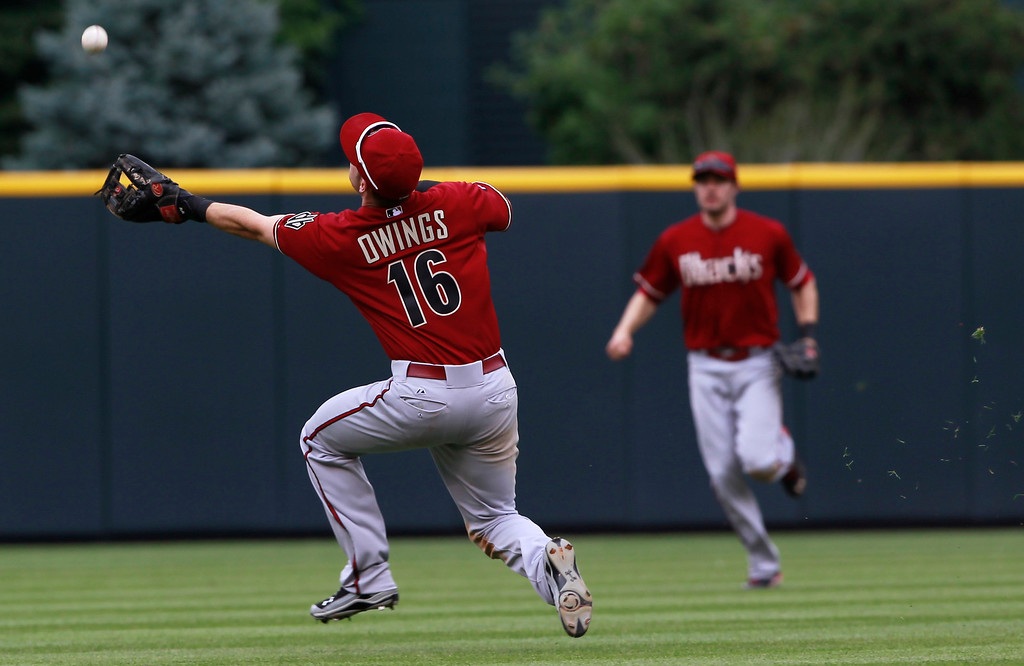 . Arizona Diamondbacks shortstop Chris Owings, front, tries to catch a pop single to drive in a runner off the bat of Colorado Rockies\' Yorvit Torrealba in the fourth inning of a baseball game in Denver on Sunday, Sept. 22, 2013. Arizona center fielder A.J. Pollock, back, looks on. (AP Photo/David Zalubowski)