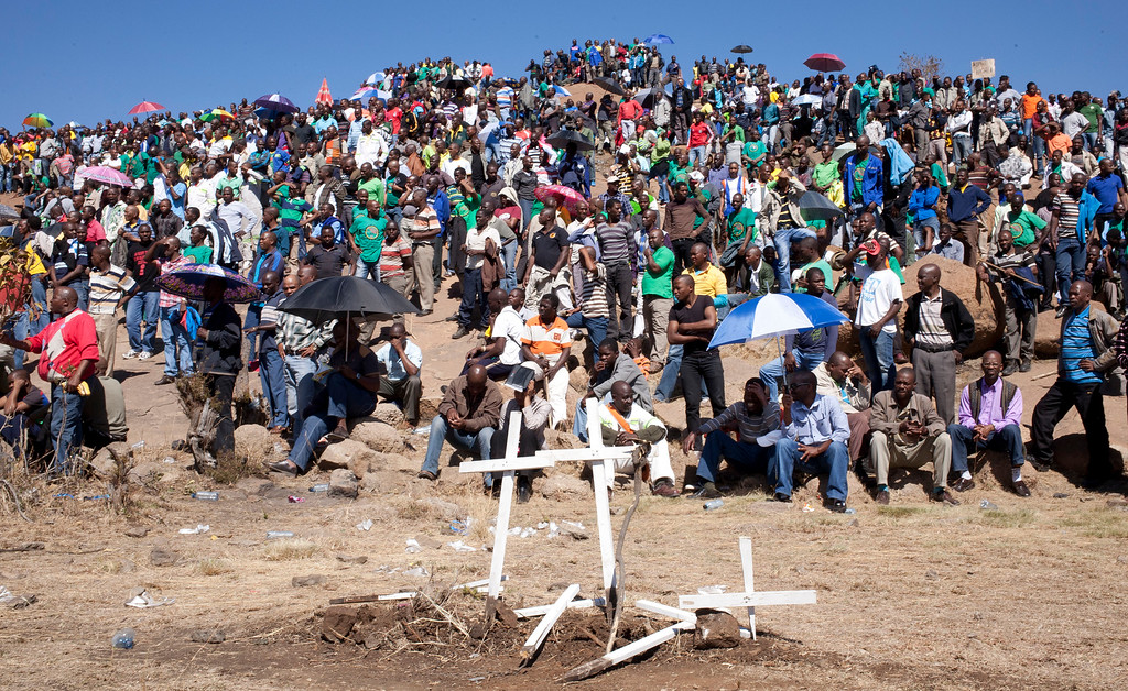 . Mine workers sit on a hill where a year ago, police opened fire on fellow workers killing 34 and injuring 78, during a memorial service to get under way, near the Marikana, South Africa, platinum mine, Friday Aug. 16, 2013. The killings happened after days of clashes with mine security and police. The miners were demanding better salaries, working, housing and living conditions. (AP Photo/Themba Hadebe)