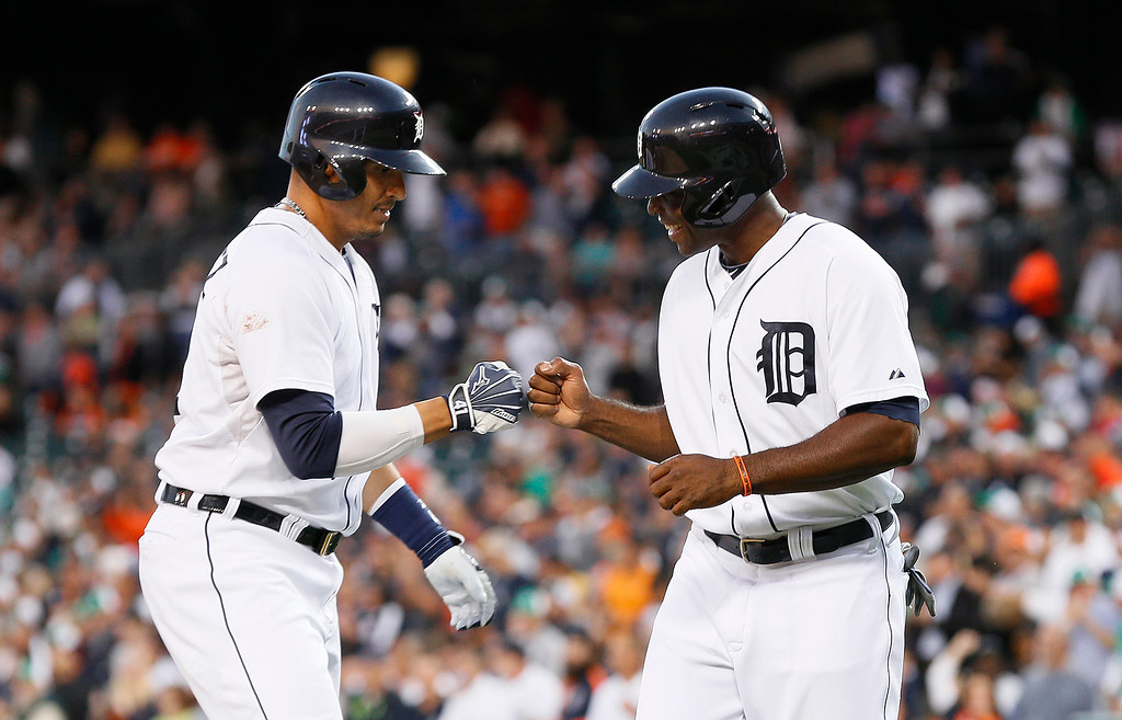 . Detroit Tigers designated hitter Victor Martinez, left, celebrates his two-run home run with teammate Torii Hunter against the Minnesota Twins in the first inning of a baseball game in Detroit, Thursday, Sept. 25, 2014. (AP Photo/Paul Sancya)