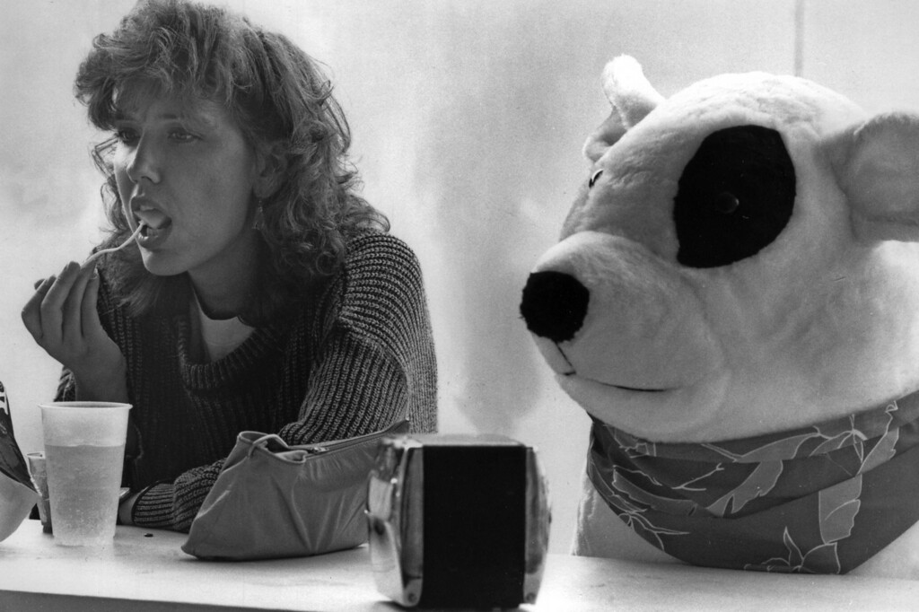 . A young woman has a bite to eat at a counter, seated next to a large stuffed bear, during the 1987 Minnesota State Fair. Photo courtesy of the Minnesota State Fair.